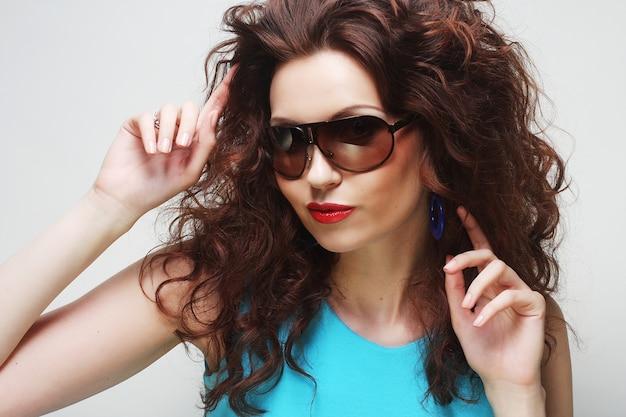 Jovem surpreendida mulher usando óculos escuros.