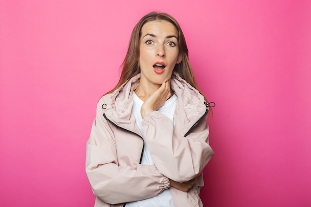 Jovem surpreendida na jaqueta rosa, fundo rosa isolado.