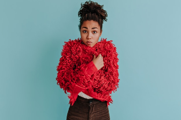 Jovem surpreendida posando com uma jaqueta ecológica vermelha