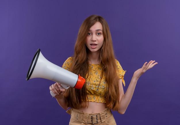 Jovem surpreendida segurando um alto-falante na parede roxa isolada