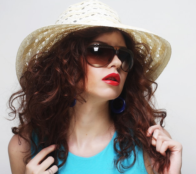Jovem surpreendida usando chapéu e óculos de sol