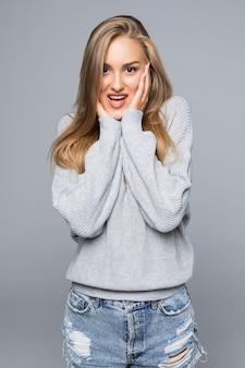 Jovem surpreendida usando um suéter quente sobre fundo cinza