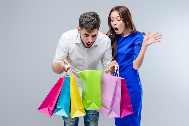 Jovem surpreendido as pessoas olham dentro de sacos de compras isolados sobre cinza