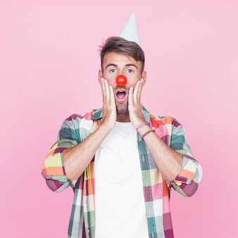 Jovem surpreendido com nariz de palhaço vermelho em pé contra o pano de fundo-de-rosa