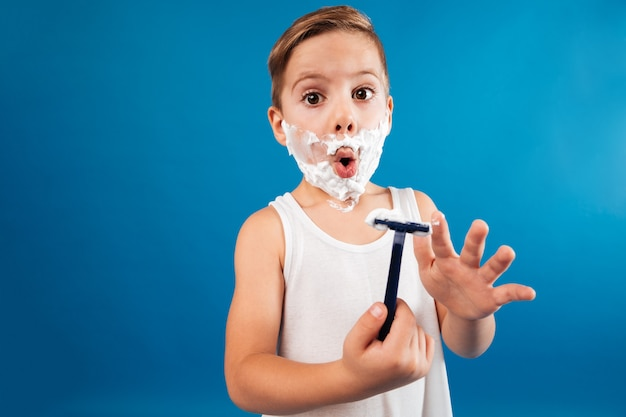 Jovem surpreendido em espuma de barbear como homem segurando a navalha