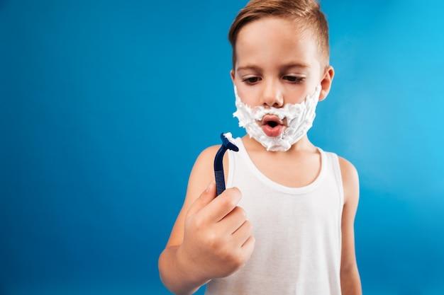 Jovem surpreendido em espuma de barbear, olhando para a navalha