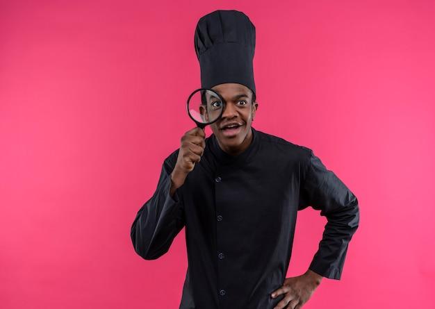 Jovem surpresa afro-americana com uniforme de chef olha através de uma lupa ou lupa isolada na parede rosa