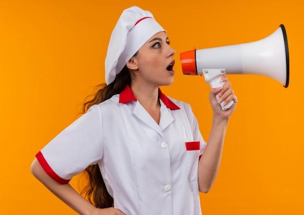 Jovem surpresa caucasiana cozinheira com uniforme de chef grita pelo alto-falante isolada na parede laranja com espaço de cópia