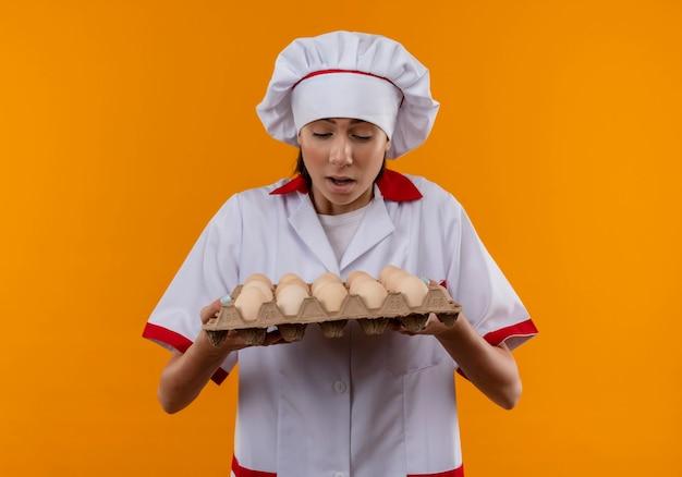 Jovem surpresa caucasiana cozinheira com uniforme de chef segura e olha para um lote de ovos em laranja com espaço de cópia