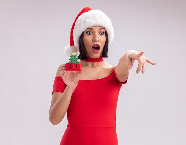 Jovem surpresa com chapéu de papai noel segurando um brinquedo da árvore de natal com um par, olhando e apontando para o lado isolado no fundo branco