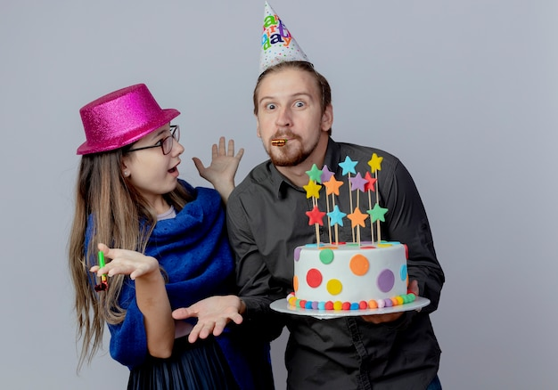 Jovem surpresa com óculos e chapéu rosa segura um apito e olha para um homem bonito surpreso com um chapéu de aniversário segurando um bolo e soprando um apito isolado na parede branca