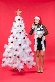 Jovem, surpresa, linda mulher com chapéu de papai noel e perto de uma árvore de natal decorada segurando presentes e ouvindo com atenção