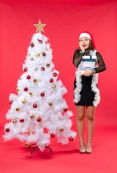 Jovem, surpresa, mulher bonita em um vestido preto com chapéu de papai noel, perto de uma árvore de natal decorada e segurando presentes