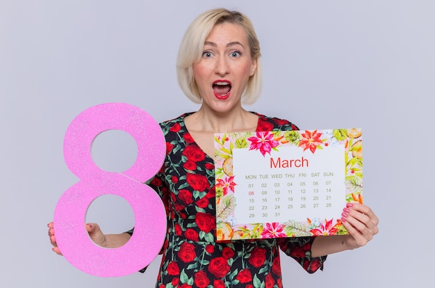 Jovem surpresa segurando o calendário do mês de março e o número oito, comemorando o dia internacional da mulher