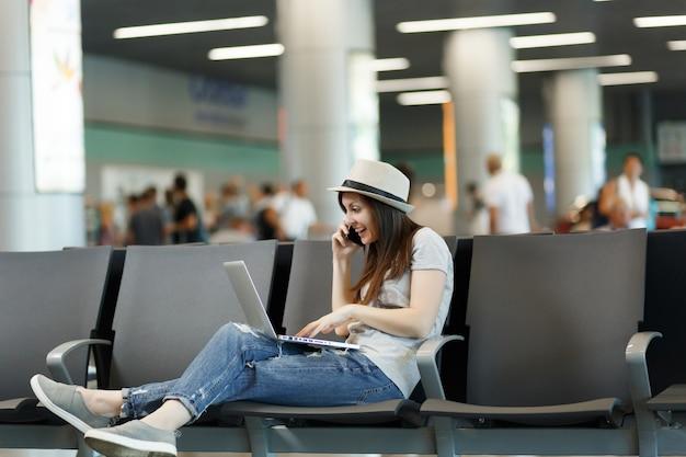 Jovem surpresa, viajante, turista, trabalhando em um laptop, falando no celular, ligando para um amigo, reservando um táxi para um hotel esperar no saguão do aeroporto