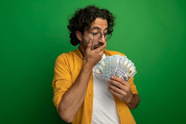 Jovem surpreso, bonito, caucasiano, usando óculos, segurando e olhando para dinheiro, mantendo a mão na boca isolada em uma parede verde com espaço de cópia
