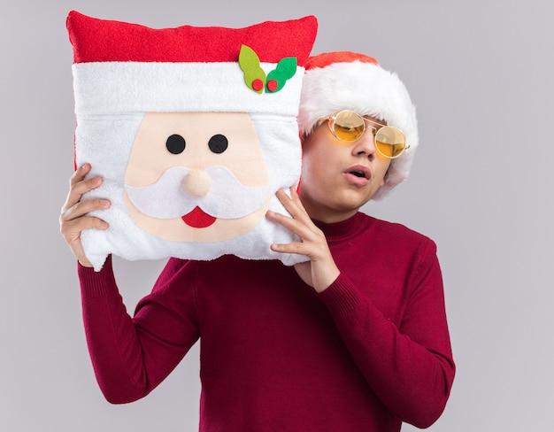 Jovem surpreso com chapéu de natal e óculos segurando uma almofada de natal isolada no fundo branco