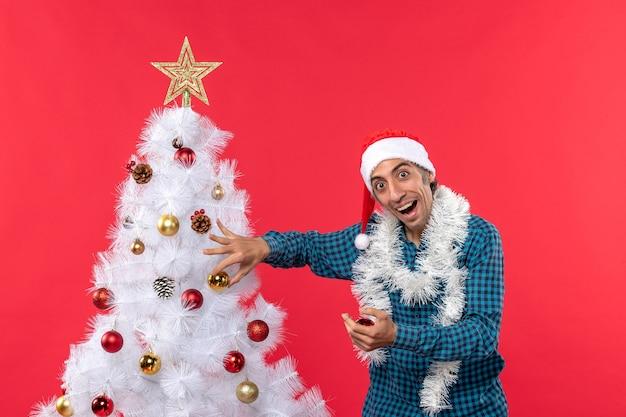 Jovem surpreso com chapéu de papai noel em uma camisa azul listrada e decorando uma árvore de natal surpreendentemente vermelha