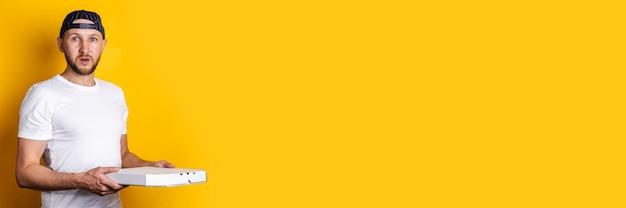 Jovem surpreso com um boné de beisebol, segurando uma caixa de pizza em uma superfície amarela. bandeira.