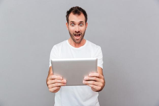 Jovem surpreso com uma camiseta branca segurando um tablet sobre um fundo cinza