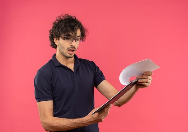Jovem surpreso de camisa preta com óculos ópticos segura e olha para a área de transferência isolada na parede rosa