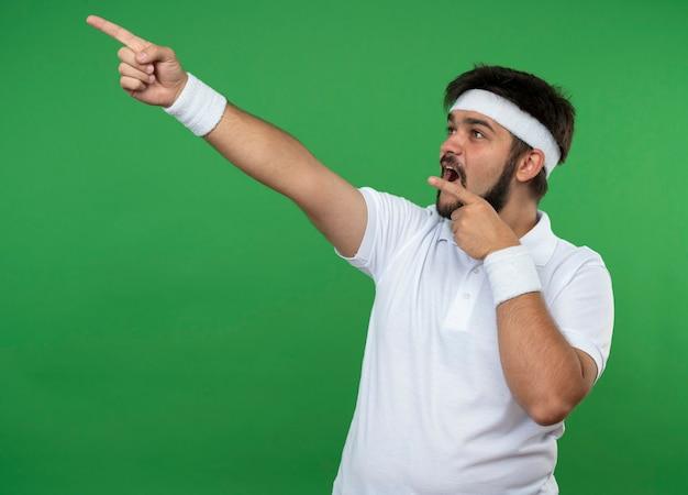 Jovem surpreso e esportivo olhando para o lado usando fita para a cabeça e pontos de pulseira na lateral isolada na parede verde