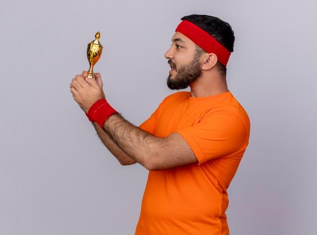 Jovem surpreso e esportivo parado na vista de perfil usando uma faixa na cabeça e segurando uma pulseira