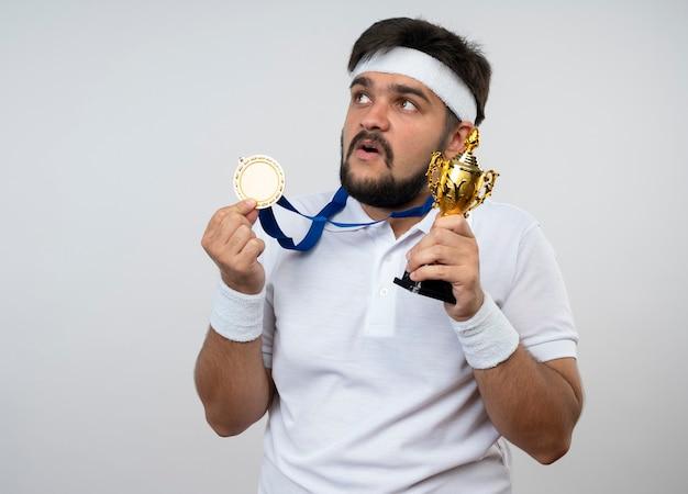 Jovem surpreso e esportivo usando bandana e pulseira, segurando a taça do vencedor e segurando a medalha isolada na parede branca