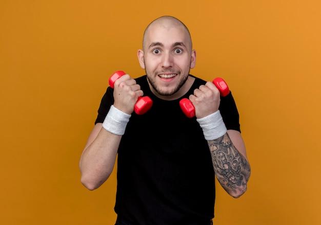 Jovem surpreso e esportivo usando pulseira, fazendo exercícios com halteres isolado em laranja