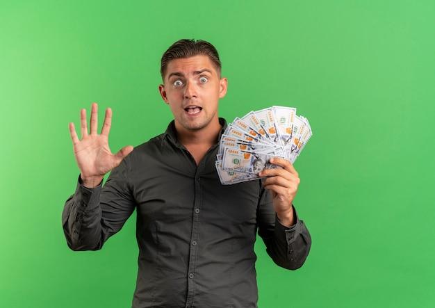 Jovem surpreso, loiro bonito gesticula cinco e segura dinheiro isolado em um espaço verde com espaço de cópia