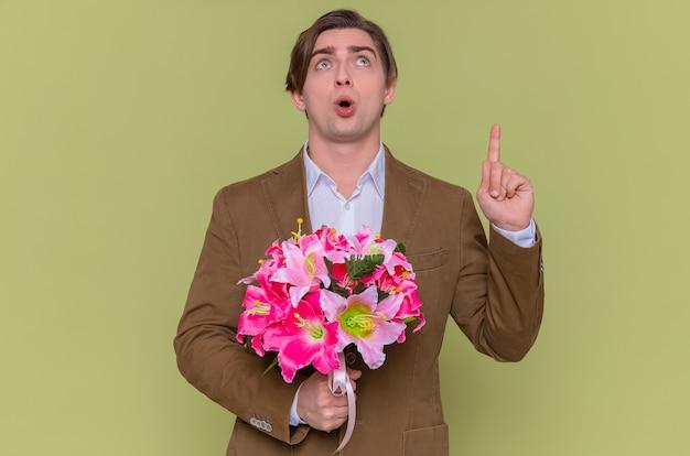 Jovem surpreso segurando um buquê de flores olhando para cima e apontando intrigado