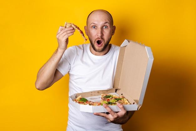 Jovem surpreso tirou um pedaço de pizza da embalagem em uma superfície amarela.