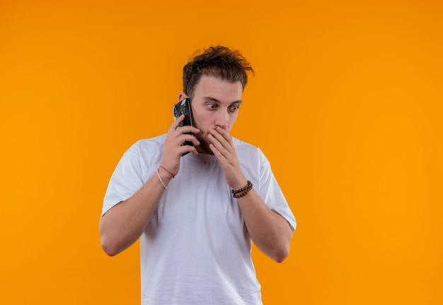 Jovem surpreso vestindo uma camiseta branca falando ao telefone e colocando a mão na boca em um fundo laranja isolado