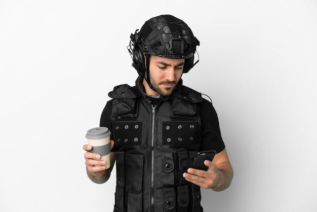 Jovem swat caucasiano isolado no fundo branco segurando um café para levar e um celular