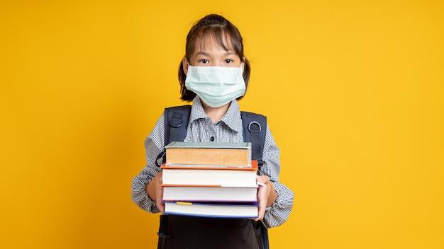 Jovem tailandesa usando máscara facial, criança asiática segurando muitos livros isolados em amarelo ou laranja