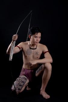 Jovem tailândia guerreiro masculino posando em uma posição de luta com um arco