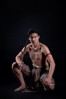 Jovem tailândia guerreiro masculino posando em uma posição de luta com uma espada