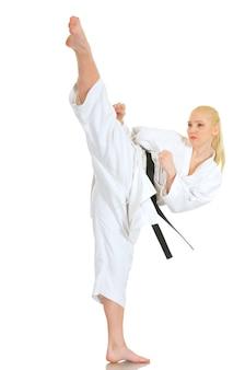 Jovem talentosa loira atleta profissional de caratê em um quimono e faixa preta mostrando um chute e um bom alongamento em um fundo branco