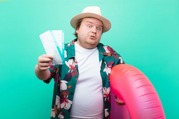Jovem tamanho grande homem com um donut inflável contra parede plana