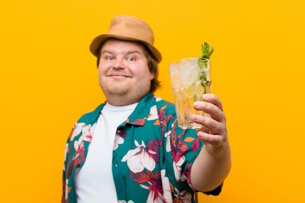 Jovem tamanho grande homem com uma bebida mojito contra parede plana