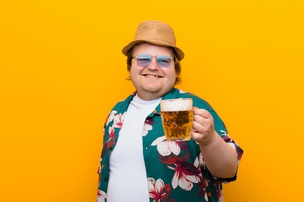 Jovem tamanho grande homem com uma caneca de cerveja contra a parede plana