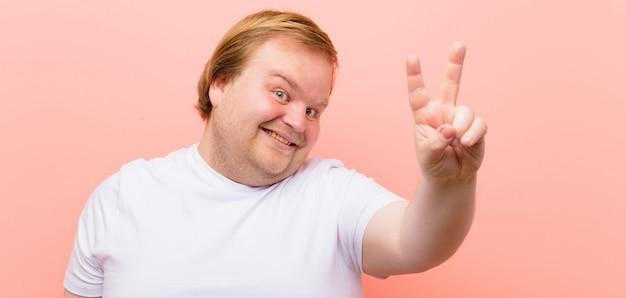 Jovem tamanho grande homem sorrindo e olhando feliz, despreocupado e positivo, gesticulando vitória ou paz com uma mão sobre parede rosa