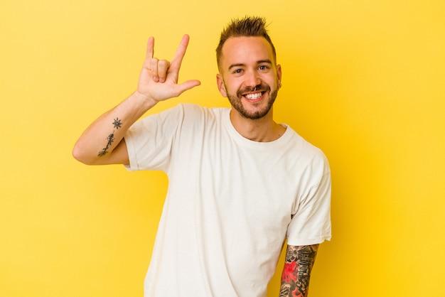 Jovem tatuado homem caucasiano isolado em um fundo amarelo, mostrando um gesto de chifres como um conceito de revolução.