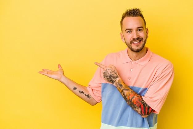 Jovem tatuado homem caucasiano isolado na parede amarela animado, segurando um espaço de cópia na palma da mão.