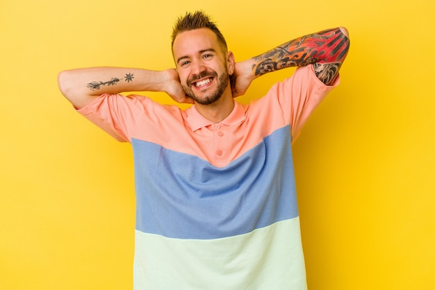 Jovem tatuado homem caucasiano isolado na parede amarela, esticando os braços, posição relaxada.