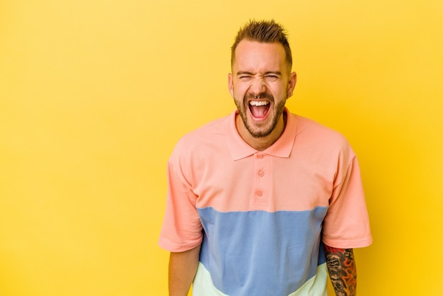 Jovem tatuado homem caucasiano isolado na parede amarela gritando com muita raiva, o conceito de raiva, frustrado.