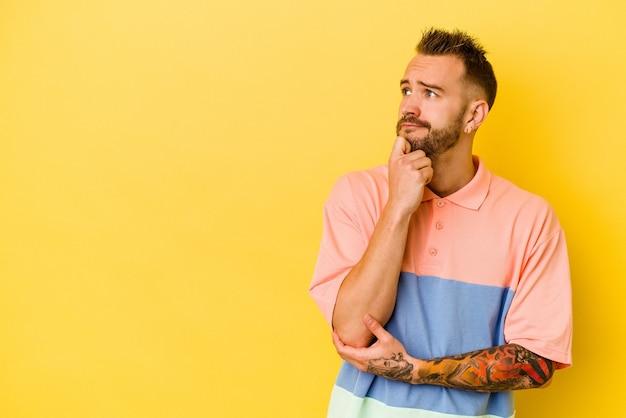 Jovem tatuado homem caucasiano isolado na parede amarela, olhando de soslaio com expressão duvidosa e cética.