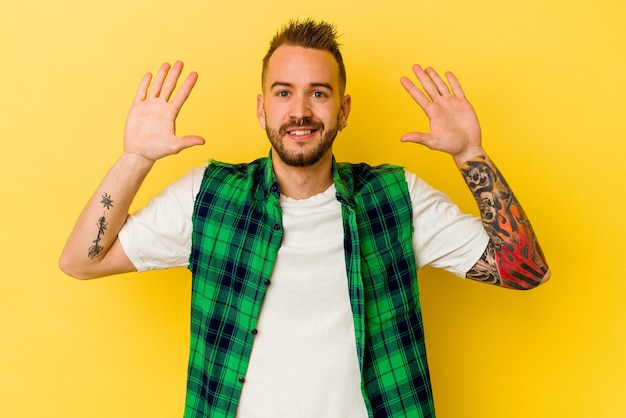 Jovem tatuado homem caucasiano isolado na parede amarela, recebendo uma agradável surpresa, animado e levantando as mãos.