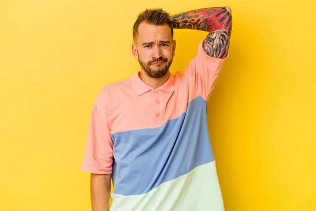 Jovem tatuado homem caucasiano isolado na parede amarela, sofrendo de dor no pescoço devido ao estilo de vida sedentário.