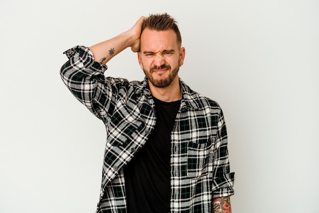 Jovem tatuado homem caucasiano isolado na parede branca, esquecendo de algo, batendo na testa com a palma da mão e fechando os olhos.